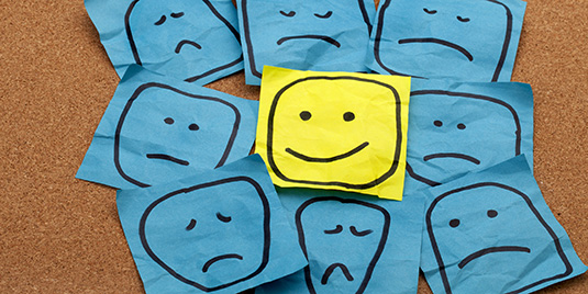 Picture of smiley face among sad faces symbolizing positive thinking with bipolar depression