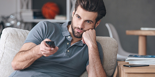 A man frowns while holding a remote aimed at the television. Represents feeling overwhelmed with news updates and politics and social media when living with bipolar.