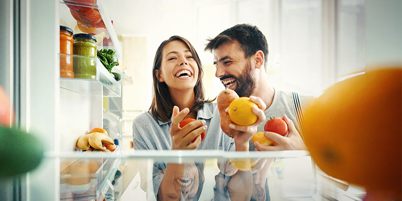 A couple laugh together, as they pull fruit and vegetables from the fridge. They're having fun and choosing healthy options.