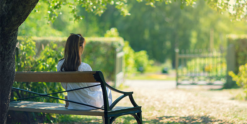 A woman sits on a bench overlooking the open gate of a cemetery. It is a sunny day, and the trees and surrounding woods are beautiful.