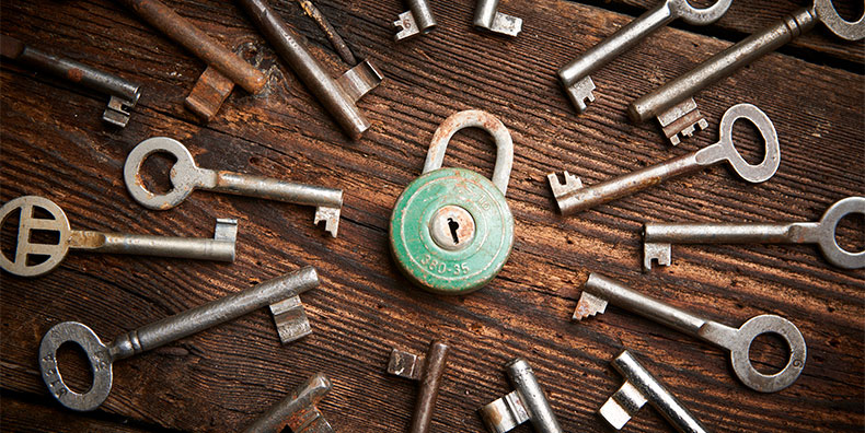 An assortment of old, rusty keys surrounds a teal lock.