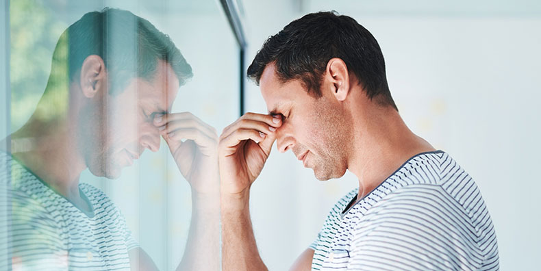 A white man in is forties stands by a window with his eyes closed, pinching the bridge of his nose. He appears downcast and disappointed. His reflection is clear in the window pane.