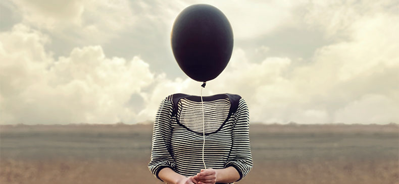 A woman stands alone in a field, with a gray sky and clouds behind her. Her shirt, arms, and hands are visible. Her collar, neck, and head are invisible. She holds a black balloon in front of her. The string's length puts the balloon in place of her invisible head.