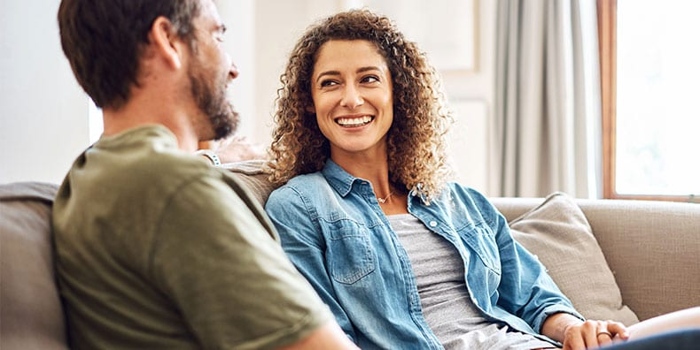 A married couple sit together on their couch, talking and smiling.