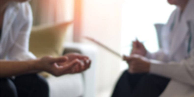 A patient sits across from a doctor who is writing something down. The image is blurred, and we see them only from the chin down to their knees. The patient seems to question or implore the doctor for understanding.
