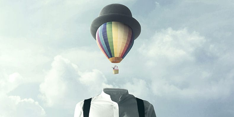 Surreal photograph of a man's shoulders in a white dress shirt with black suspenders and an invisible neck and head. His head is replaced by a colorful hot-air balloon that is wearing his hat. He is in the basket of the hot-air balloon, looking to the left with a periscope. Represents changing cognition and self-awareness with bipolar disorder.