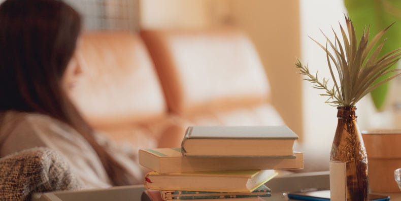 A woman rests on a sofa in the background. She is blurred out. The sun is shining through a window to the right. There is a stack of books beside her on the table. Represents the importance of adequate sleep and rest with bipolar.