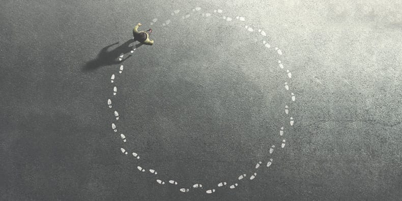 A man retraces his footsteps in a big circle. Represents ruminating and obsessive thought loops with bipolar disorder, anxiety, and depression.
