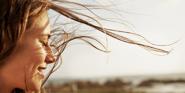 With windswept hair, a woman smiles into the sun, representing looking for the positives or benefits of managing bipolar disorder