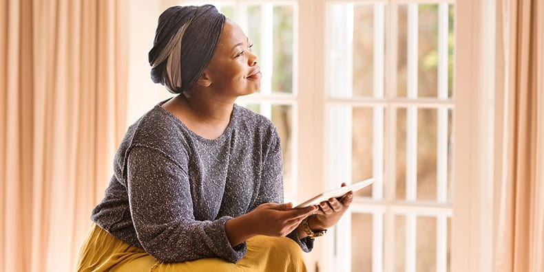 A woman of color smiles by a window, represents accepting a bipolar disorder diagnosis.
