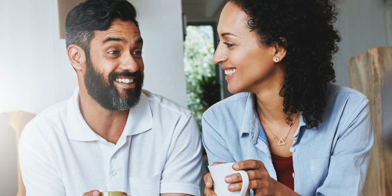 A man and woman in their midthirties or early forties share a cup of coffee on the stoop of their home. They're smiling midconversation. Represents being a newlywed or new partner while managing bipolar symptoms.