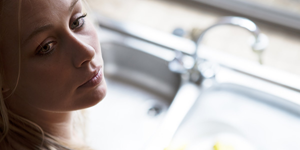 A woman looks over her shoulder with a longing expression on her face. Blurred in the background is the kitchen sink, with one side filled with soapy water.