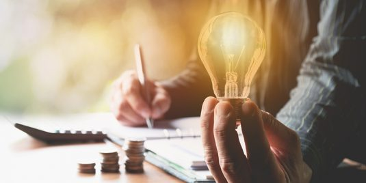 An entrepreneur with bipolar disorder holding a lightbulb while he works