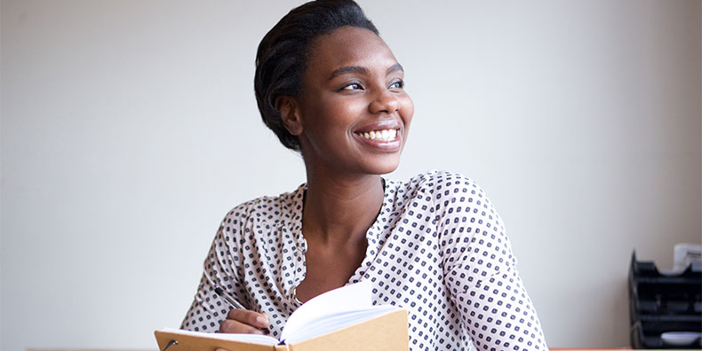 A woman of color looks off to the left. Her face is lit by sunlight. She is smiling peacefully while seated and writing in a journal.