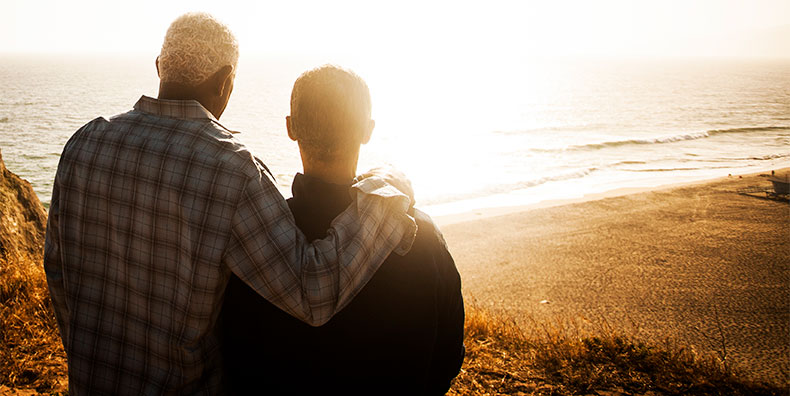 An older man of color places his arm around another as they look out at the sunset over the beach. We see them only from behind. They are peaceful and forgiving.