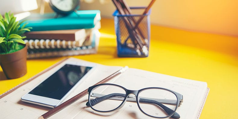 A bright yellow desk with an open planner, smartphone, pencil, glasses, plant, clock, and stack of journals.