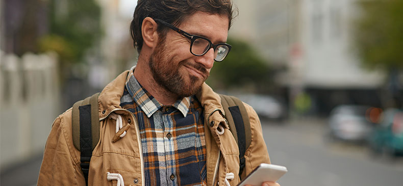 A white man in his mid-thirties looks skeptically at his phone. He's walking down a city sidewalk. The background is blurred. He is wearing black glasses and has a full beard and mustache.