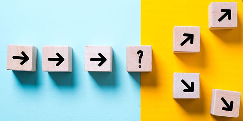 A series of brown blocks with arrows are arranged on a plane. The left half is a teal background; the right is yellow. In the middle sits a block with a question mark on it. A row of arrow blocks leads to the question mark. From there, two branches of arrows split off, with one going upward to the top right corner and one going downward to the bottom right corner.