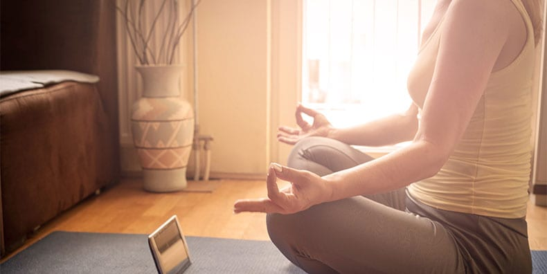 A woman listens to a guided meditation while seated in lotus position on a yoga mat in her living room.