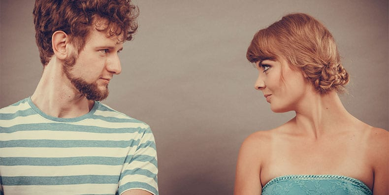 Two people stand side by side against a gray background. Their bodies face forward, but their faces are in profile as they look each other in the eyes.
