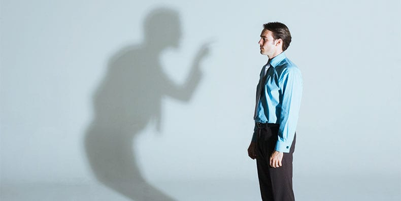A man is being scolded by his own shadow. A man seen in profile stands with his arms down, looking straight ahead, to the left of the image. Behind him on the wall, his shadow is turning toward him, scolding him, and pointing its finger in his face.