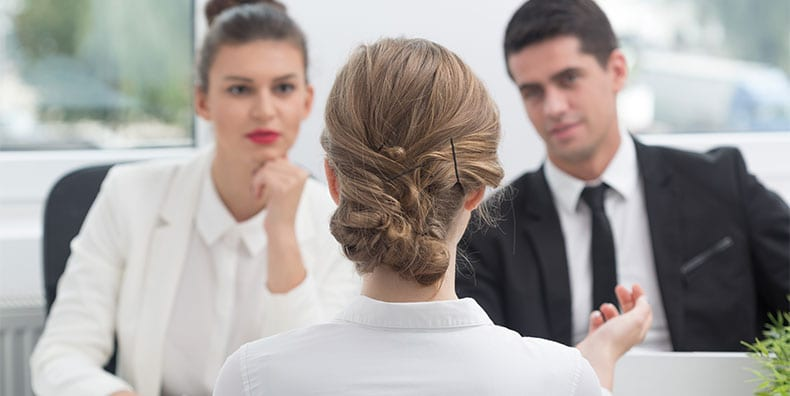 A woman, seen from behind, is applying for a job. She's seated at a table and gesturing with her hand. We see the back of her head and shoulders. Behind her, two interviewers are blurred in the background. They're in suits and look at the woman intently.