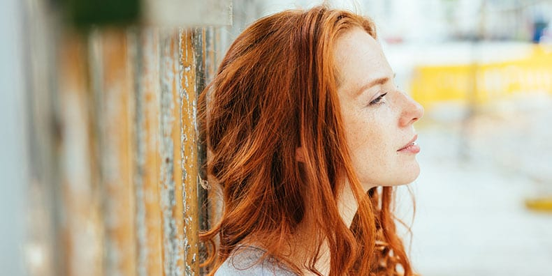 A woman with long red hair leans against a wooden fence outdoors. She's facing to the right, with her face uplifted and a thoughtful expression.
