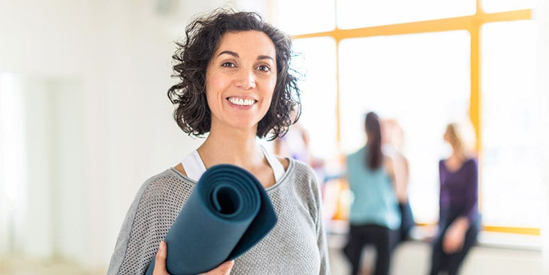 A middle-aged woman smiles, holding her rolled-up yoga mat after class.
