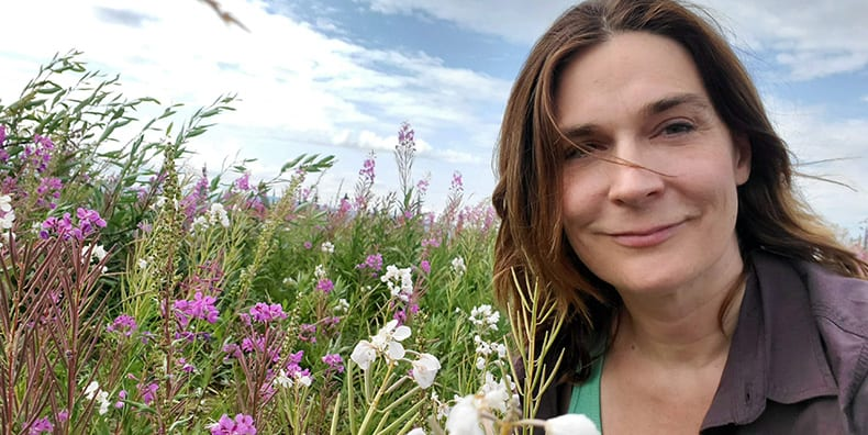 Carin smiles as she sits in a field of springtime flowers. The wind is blowing and a bird takes flight in the distance. Represents finding stability with bipolar mood episodes despite seasonal triggers.