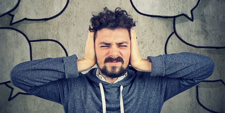 A man squeezes his hands to his ears, with his face scrunched up. In the background are the outlines of many speech bubbles. Represents having bipolar and being highly sensitive to stress and different triggers.