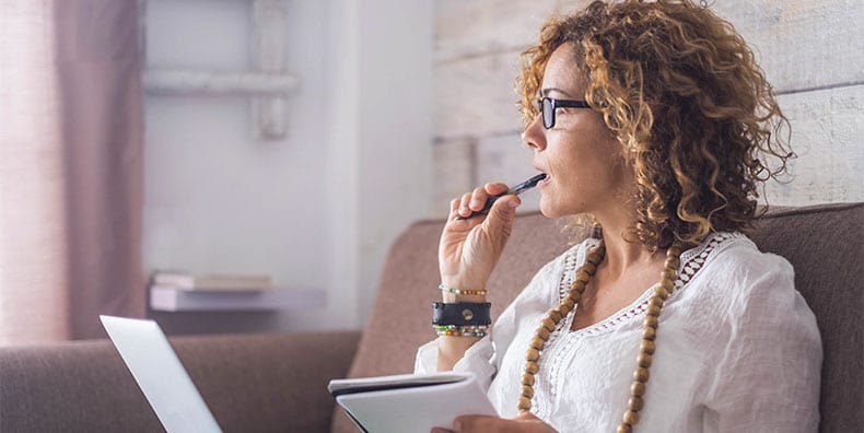 A woman pauses to reflect while writing. Represents a person learning to accept the diagnosis of bipolar and its implications. Both strengths and limitations.